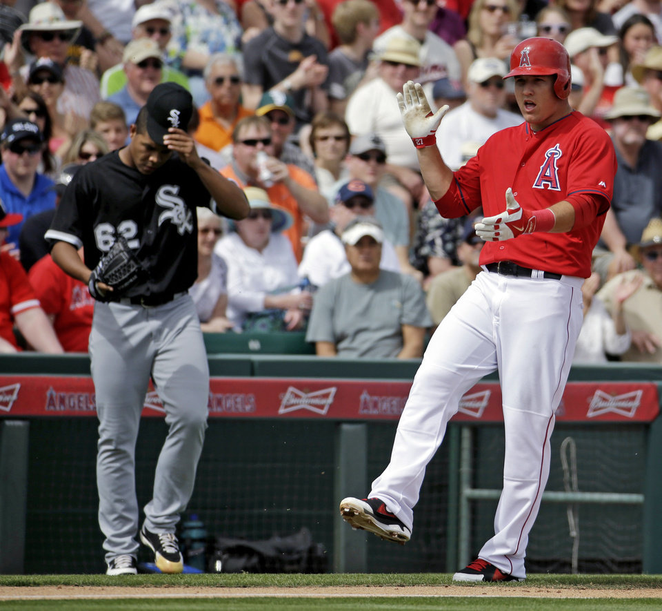 Photo - Los Angeles Angels' Mike Trout reacts from third in front of Chicago White Sox's Jose Quintana (62) after Trout hit a triple during the first inning of an exhibition spring training baseball game Thursday, March 13, 2014, in Tempe, Ariz. (AP Photo/Morry Gash)