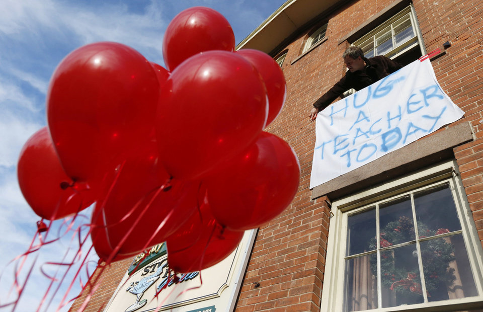 Gary Seri, general manager at the Stone River Grille, hangs a message written on a table cloth in honor of the teachers who died along with students a day earlier when a gunman open fire at Sandy Hook Elementary School, Saturday, Dec. 15, 2012, in the Sandy Hook village of Newtown, Conn. Seri, who put up red balloons that were not used when a sweet 16 party was canceled the night before in light of the massacre, said the teachers were scheduled to have their holiday party at his restaurant. The massacre of 26 children and adults at Sandy Hook Elementary school elicited horror and soul-searching around the world even as it raised more basic questions about why the gunman, 20-year-old Adam Lanza, would have been driven to such a crime and how he chose his victims. (AP Photo/Julio Cortez) ORG XMIT: CTJC111