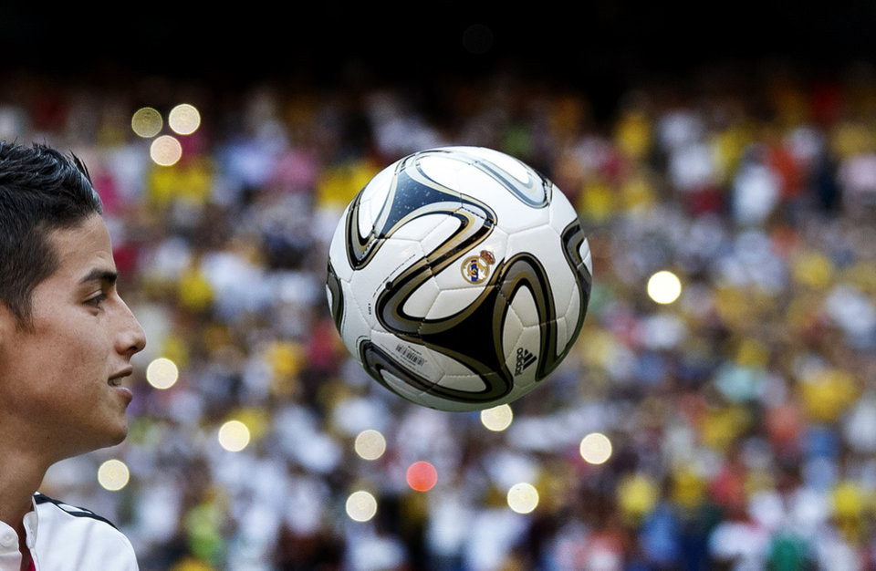 Photo - New Real Madrid player James Rodriguez, from Colombia, plays with a ball as he poses for photographers during his official presentation at the Santiago Bernabeu stadium in Madrid, Spain, Tuesday, July 22, 2014, after signing for Real Madrid. Real Madrid have signed Rodriguez from Monaco on a six-year contract,  (AP Photo/Daniel Ochoa de Olza)