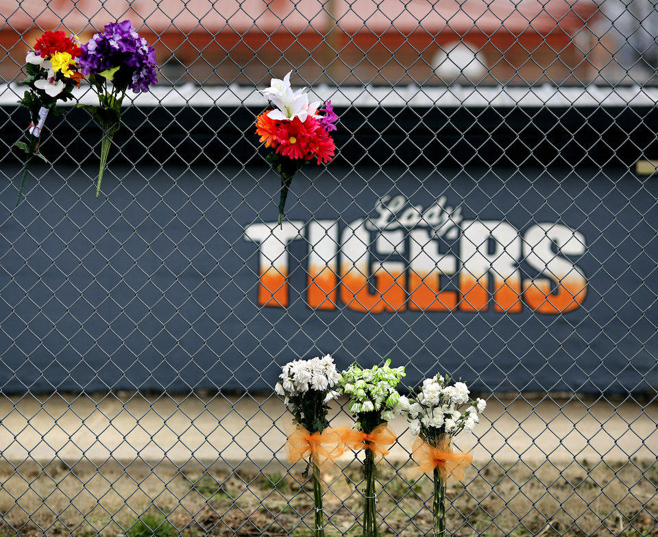 Photo - Flowers and personalized notes are placed on a chain-link fence near the home dugout of the Konawa softball stadium. Konawa Middle School athlete Rhindi Kay Isaacs, 12, was among three people who died in a fiery, head-on collision Friday evening. The Konawa Public School District said six students from the  junior high school girls softball team were aboard the bus  traveling home at the time of the crash. The team's coach was driving the bus when it was struck by an SUV on SH 377, between Bowlegs and Konawa, in Seminole County. The Oklahoma Highway Patrol said the SUV was traveling in the northbound lane just after 7 p.m. when it swerved and collided with a Konawa School activity bus after the driver of the SUV swerved when passing another vehicle, 