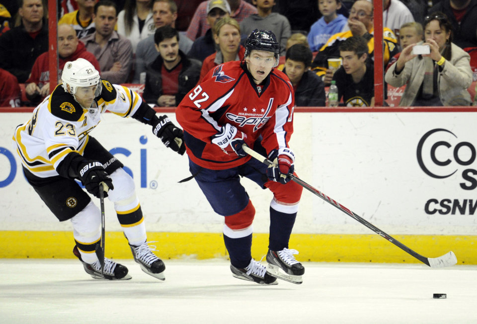 Photo - Washington Capitals center Evgeny Kuznetsov (92), of Russia, works the puck up ice against Boston Bruins center Chris Kelly (23) during the first period of an NHL hockey game, Saturday, March 29, 2014, in Washington. (AP Photo/Nick Wass)