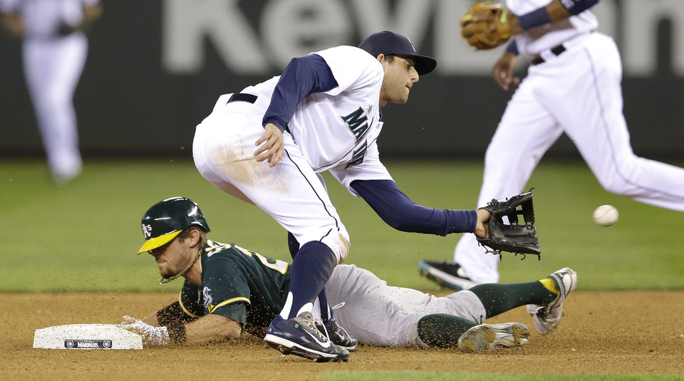 Photo - Oakland Athletics' Eric Sogard, left, is safe stealing second as Seattle Mariners shortstop Brad Miller waits for the throw in the sixth inning of a baseball game on Saturday, April 12, 2014, in Seattle. (AP Photo/Ted S. Warren)