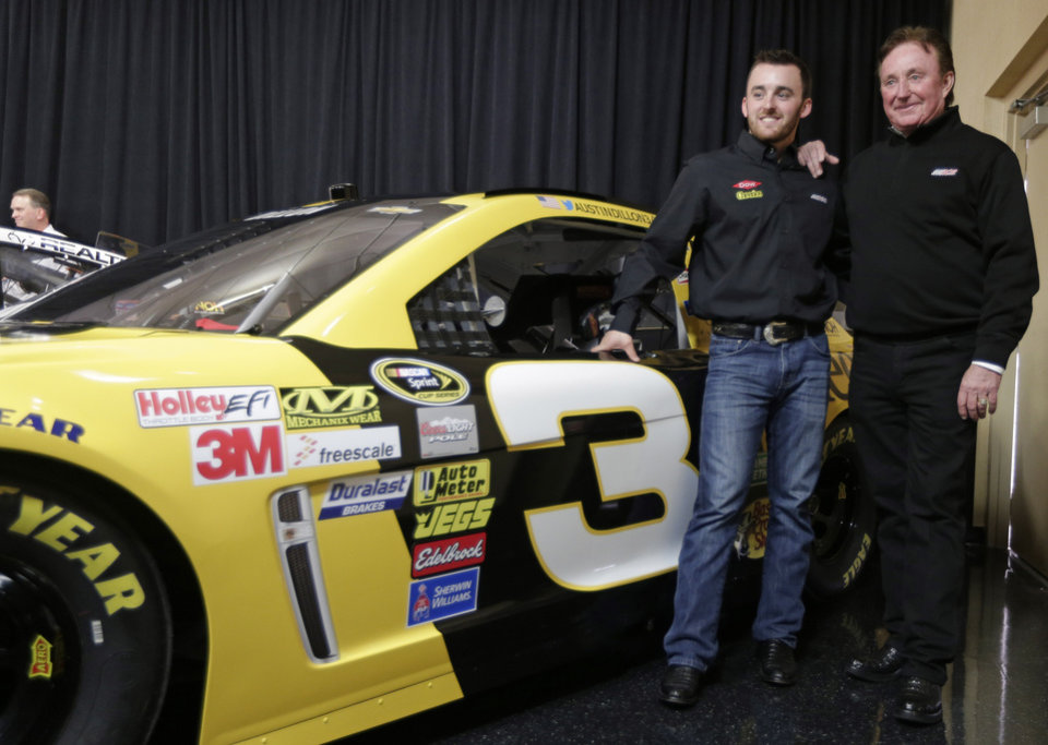 Photo - Austin Dillon, left, and team owner Richard Childress, right, pose by one of the cars Dillon will drive in the 2014 NASCAR Sprint Cup series during a news conference at Charlotte Motor Speedway in Concord, N.C., Wednesday, Dec. 11, 2013. The late Dale Earnhardt's famed No. 3 will be back on track in the elite Sprint Cup Series next season with Dillon using the number. (AP Photo/Chuck Burton)