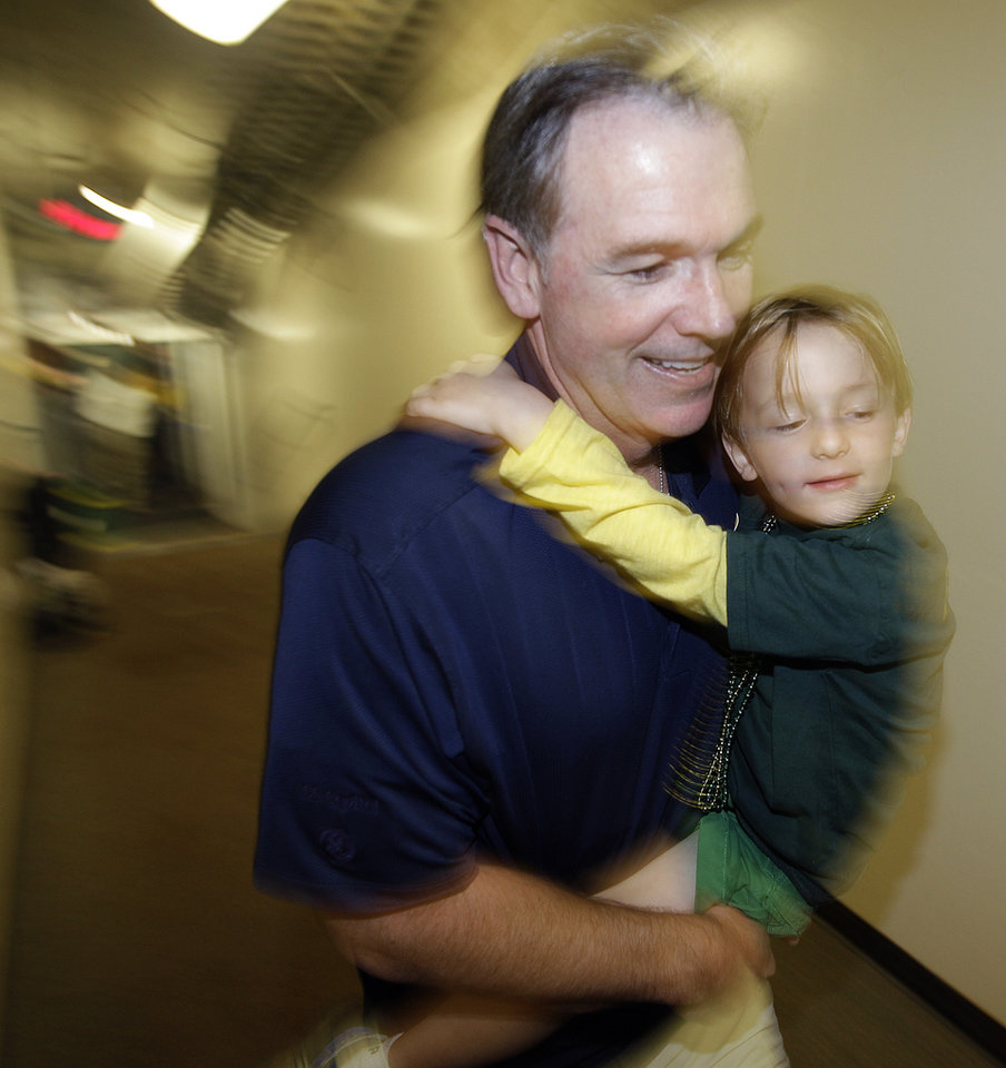 Photo -   Oakland Athletics general manager Billy Beane carries a child as he heads to the clubhouse after the A's clinched the AL West title when they defeated the Texas Rangers 12-5 in a baseball game, Wednesday, Oct. 3, 2012, in Oakland, Calif. (AP Photo/Ben Margot)