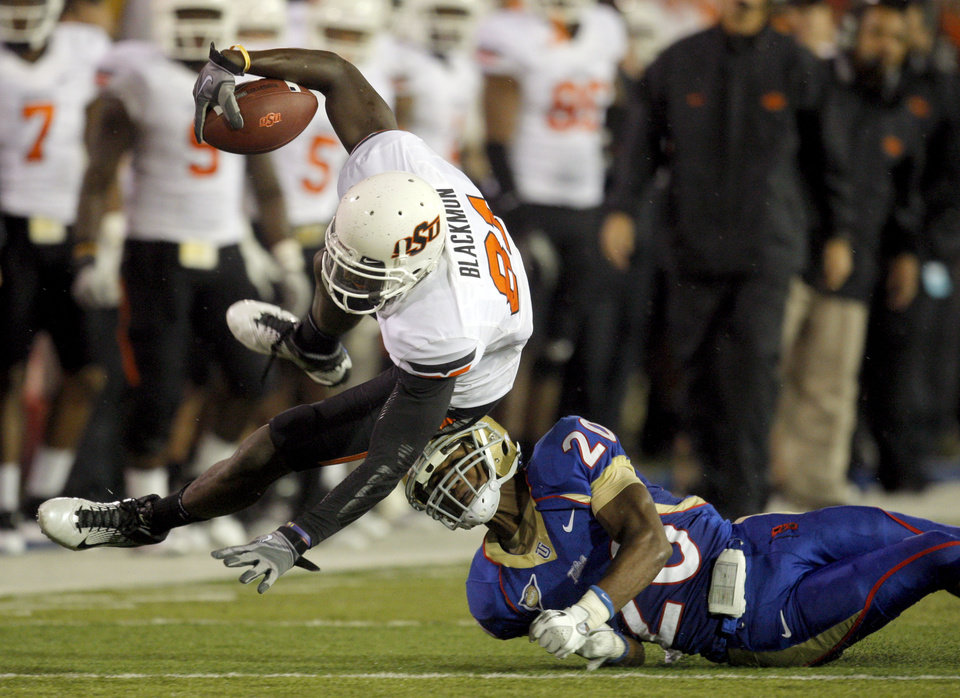 Photo - Oklahoma State's Justin Blackmon (81) leaps over Tulsa's Marco Nelson (20)during the third quarter of the college football game between the Oklahoma State University Cowboys and the University of Tulsa Golden Hurricane at H.A. Chapman Stadium in Tulsa, Okla., Sunday, Sept. 18, 2011. Photo by Sarah Phipps, The Oklahoman