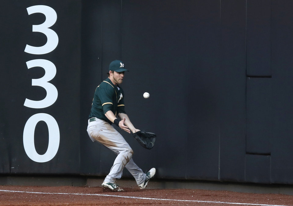 Photo - Oakland Athletics right fielder Josh Reddick tries to field New York Mets' Eric Campbell's second-inning double off the right field wall in an interleague baseball game in New York, Tuesday, June 24, 2014. (AP Photo/Kathy Willens)