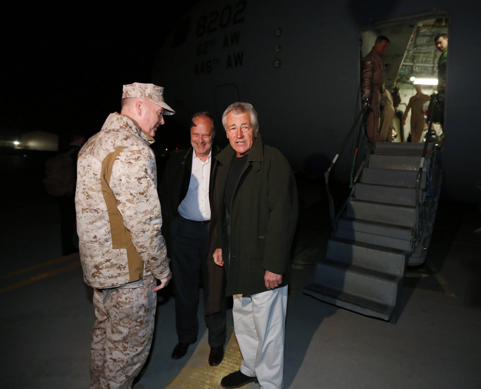 Photo - Defense Secretary Chuck Hagel is greeted by U.S. Ambassador to Afghanistan James Cunningham, center, and Gen. Joseph Dunford, Commander of the International Security Force upon Hagel's arrival in Kabul, Afghanistan, Friday, March 8, 2013. Hagel arrived in Afghanistan Friday for his first visit as Pentagon chief, saying that there are plenty of challenges ahead as NATO hands over the country's security to the Afghans.  (AP Photo/Jason Reed, Pool)