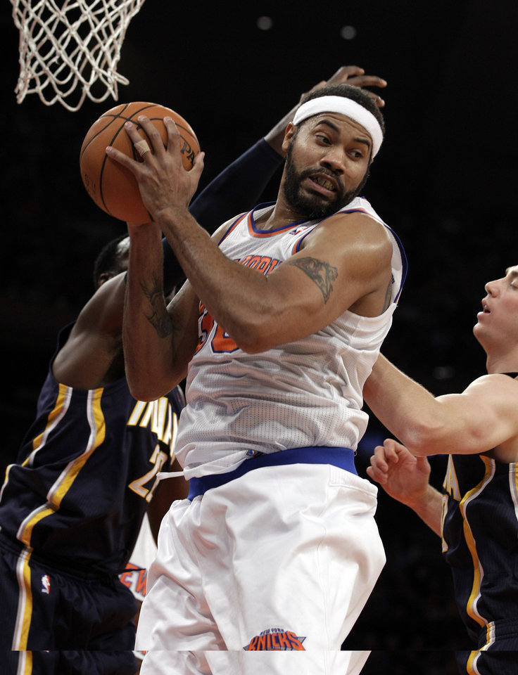 New York Knicks center Rasheed Wallace pulls down a rebound against the defense of the Indiana Pacers in the first half of their NBA basketball game at Madison Square Garden in New York, Sunday, Nov. 18, 2012. (AP Photo/Kathy Willens)