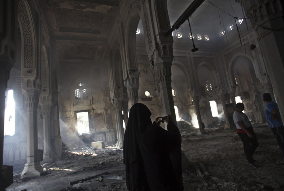 Photo - Egyptians inspect the inside of the burned Rabaah al-Adawiya mosque, where supporters of Egypt's ousted President Mohammed Morsi had a protest camp in Nasr City, Cairo, Egypt, Thursday, Aug. 15, 2013. Egypt faced a new phase of uncertainty on Thursday after the bloodiest day since its Arab Spring began, with hundreds people reported killed and thousands injured as police smashed two protest camps of supporters of the deposed Islamist president. Wednesday's raids touched off day-long street violence that prompted the military-backed interim leaders to impose a state of emergency and curfew, and drew widespread condemnation from the Muslim world and the West, including the United States. (AP Photo/Khalil Hamra)