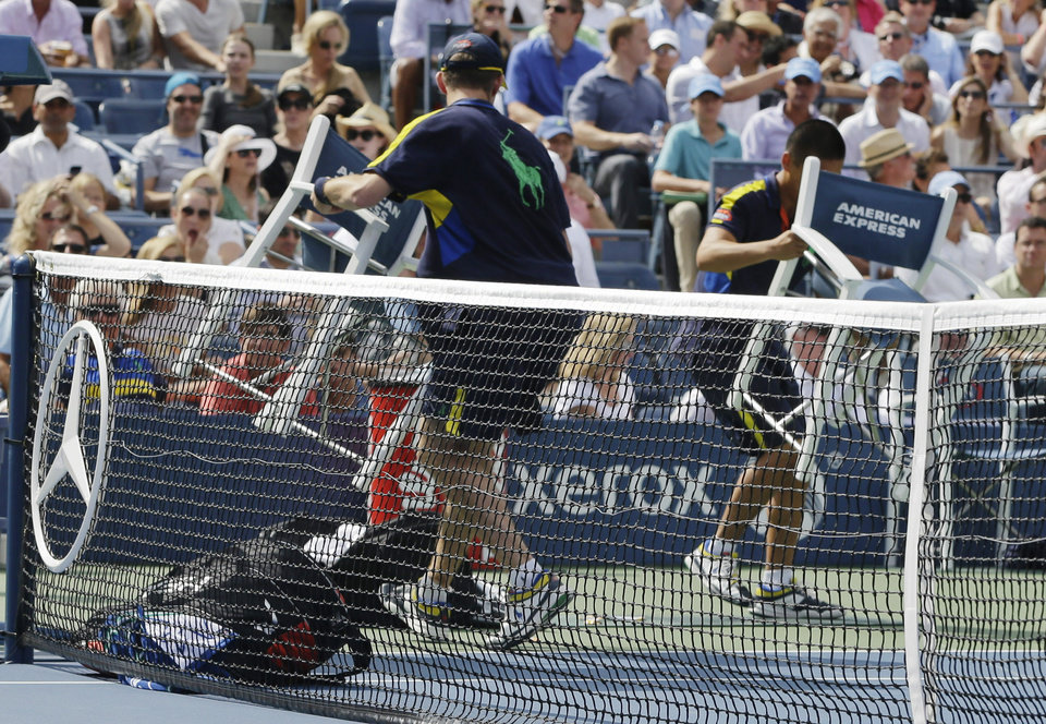 Photo -   Ball persons return chairs and tennis gear to the sidelines after a gust of wind blew them onto the court during a semifinal match between Britain's Andy Murray and Tomas Berdych, of the Czech Republic, at the 2012 US Open tennis tournament, Saturday, Sept. 8, 2012, in New York. (AP Photo/Darron Cummings)