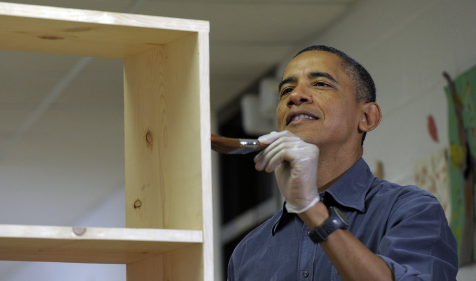 Photo - President Barack Obama stains a bookshelf at Burrville Elementary School in Washington, Saturday, Jan. 19, 2013, as the first family participated in a community service project for the National Day of Service, part of the 57th Presidential Inauguration. (AP Photo/Susan Walsh)