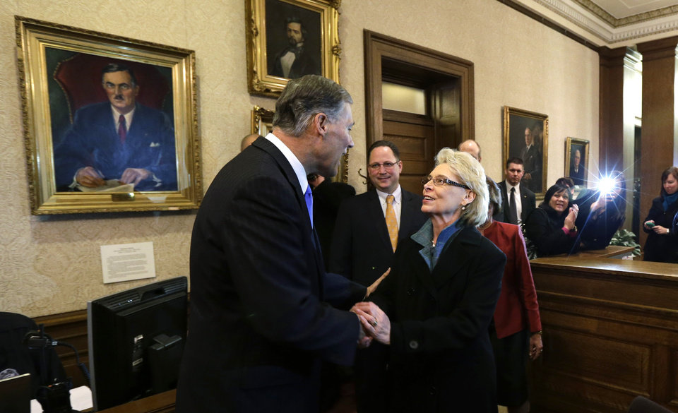 Gov. Jay Inslee, left, is greeted by former Gov. Chris Gregoire, right, in the governor\'s office after Inslee was sworn in as Governor, Wednesday, Jan. 16, 2013, at the Capitol in Olympia, Wash. Gregoire served two terms as Governor. (AP Photo/Ted S. Warren)