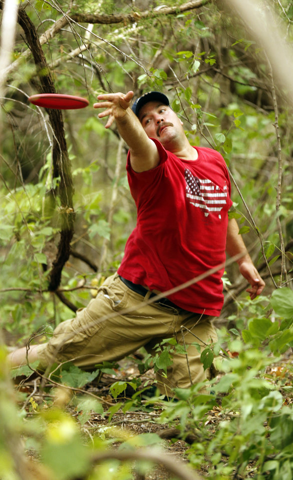 Photo - Andy Newberry, Wichita Falls, Texas, hooks a shot from heavy brush during the Kenneth Brent Edwards Memorial disc golf tournament in Norman on Saturday, July 7, 2012, in Norman, Okla.  Photo by Steve Sisney, The Oklahoman