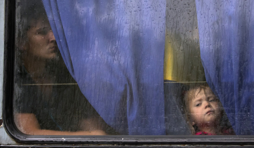 Photo - People look through a bus window as they depart as refugees to Russia in the city of Donetsk, eastern Ukraine Monday, July 14, 2014. Five busloads of Internally Displaced People from the towns of Slavyansk, Karlovka, Maryinka and Donetsk left here Monday morning for the Rostov region in Russia to ask for refugee status there. (AP Photo/Dmitry Lovetsky)