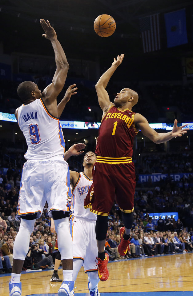 Photo - Cleveland's Jarrett Jack (1) shoots over Oklahoma City's Serge Ibaka (9) during the NBA basketball game between the Oklahoma City Thunder and the Cleveland Cavaliers at the Chesapeake Energy Arena in Oklahoma City, Okla. on Wednesday, Feb. 26, 2014.  Photo by Chris Landsberger, The Oklahoman