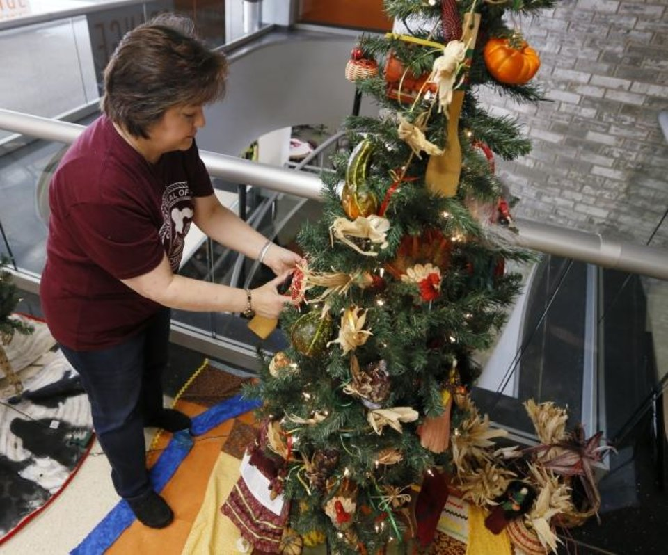 Photo -  Susan Howard decorates the Muscogee (Creek) Nation Christmas tree for Red Earth Treefest at the OSU-OKC Student Center in Oklahoma City, Monday, Dec. 2, 2019. [Nate Billings/The Oklahoman]