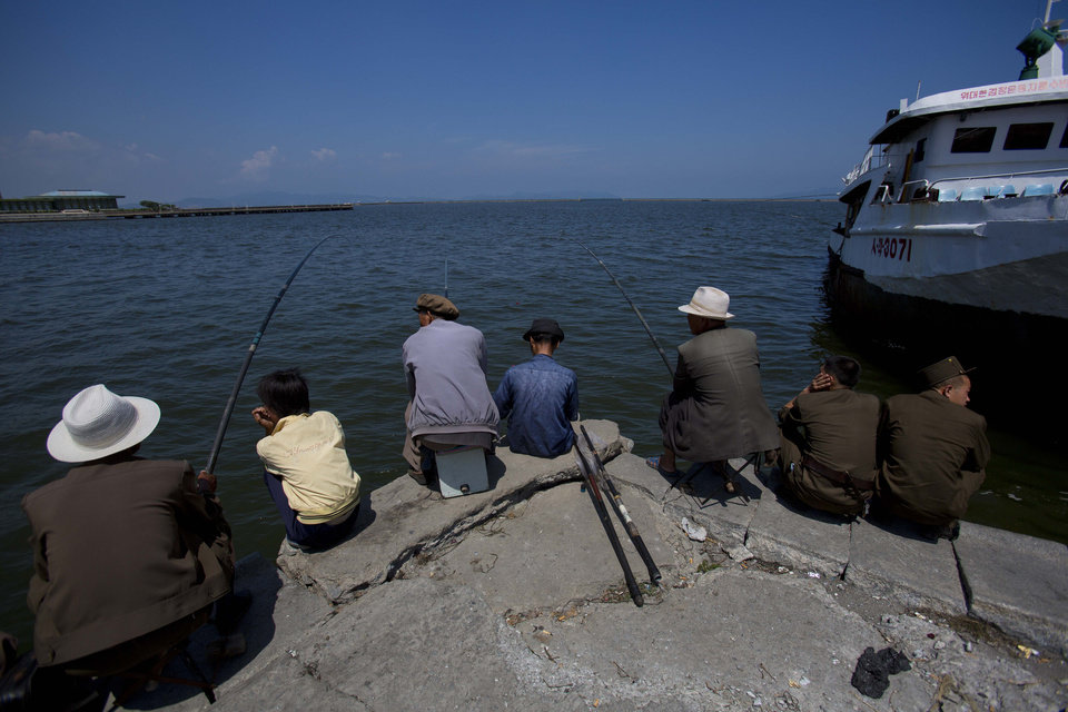 In this Aug. 9, 2012 photo, people fish at the port in Wonsan, North Korea. (AP Photo/David Guttenfelder)