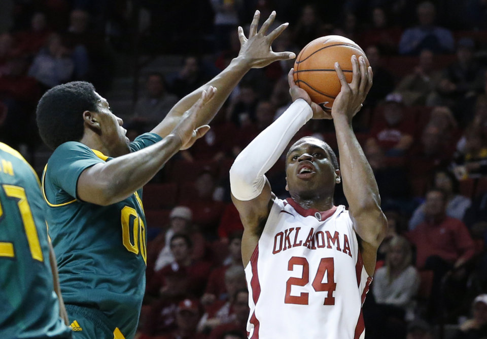 Photo - Oklahoma guard Buddy Hield (24) fakes a shot before passing to a teammate in front of Baylor forward Royce O'Neale (00) in the second half of an NCAA college basketball game in Norman, Okla., Saturday, Feb. 8, 2014. Oklahoma won 88-72. (AP Photo/Sue Ogrocki)