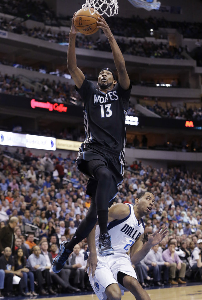 Photo - Minnesota Timberwolves forward Corey Brewer (13) scores a basket against Dallas Mavericks guard Devin Harris (20) during the first half an NBA basketball game Wednesday, March 19, 2014, in Dallas. (AP Photo/LM Otero)