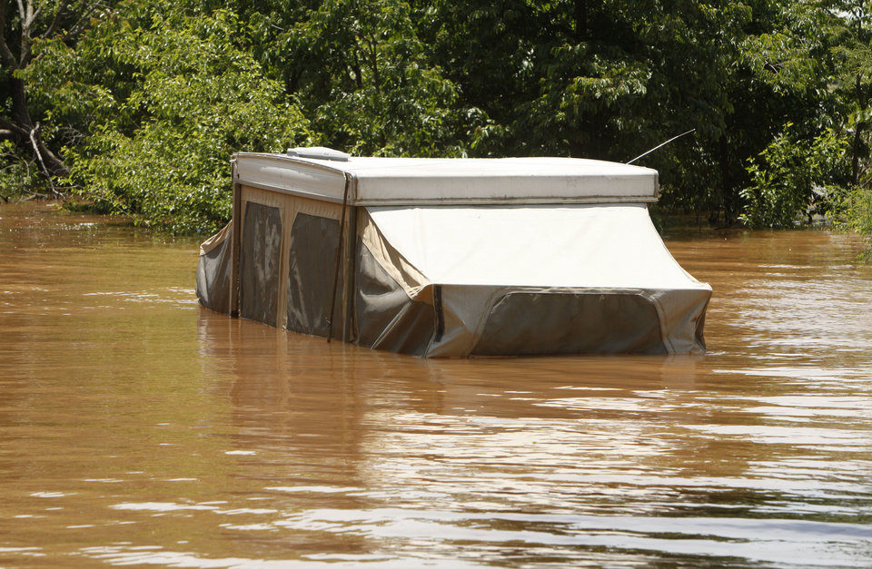 Photo - A pop-up camper was submerged in the floodwaters at Arcadia Lake. The owners couldn't get it out of a Central State Park campground before the area flooded from Friday's storms. PHOTO BY PAUL HELLSTERN, THE OKLAHOMAN.  PAUL HELLSTERN - THE OKLAHOMAN