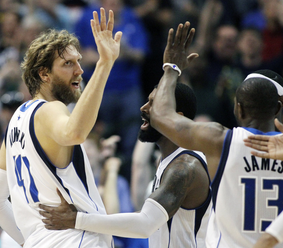 Photo - Dallas Mavericks forward Dirk Nowitzki (41), of Germany, celebrates with teammates O.J. Mayo, center, and Mike James (13) after scoring the game-winning basket during the second half of an NBA basketball game, Saturday, March 30, 2013, in Dallas. Dallas defeated Chicago 100-98. (AP Photo/Michael Mulvey)
