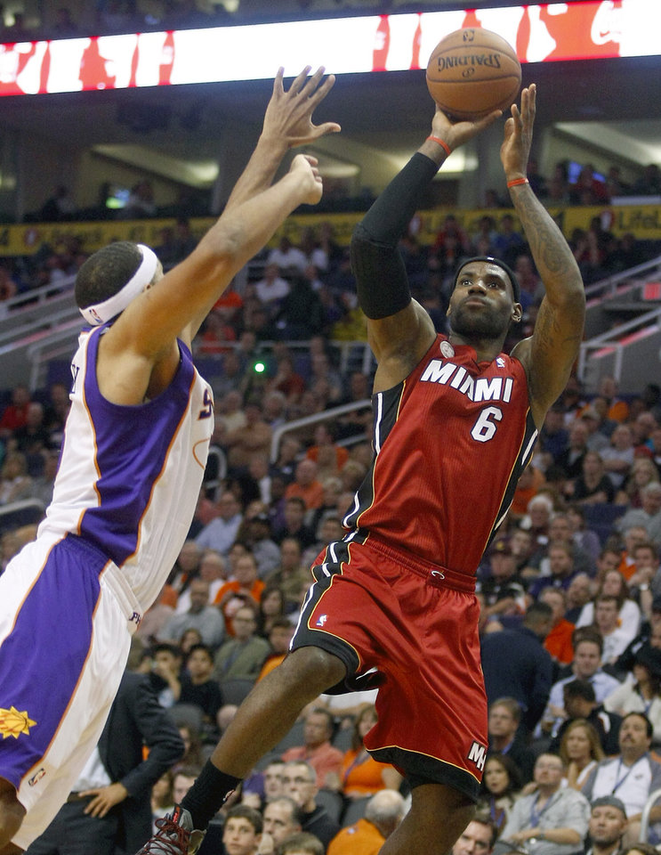 Miami Heat forward LeBron James (6) shoots and scores over Phoenix Suns guard Jared Dudley (3) in the first quarter during an NBA basketball game on Saturday, Nov. 17, 2012, in Phoenix. (AP Photos/Matt York)