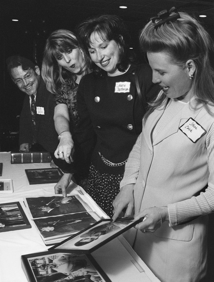 Photo - Looking at old photos of Danny Williams are, from left, Bob Brown, Michelle Winters, Laurie Patterson and Stacie Cadle.