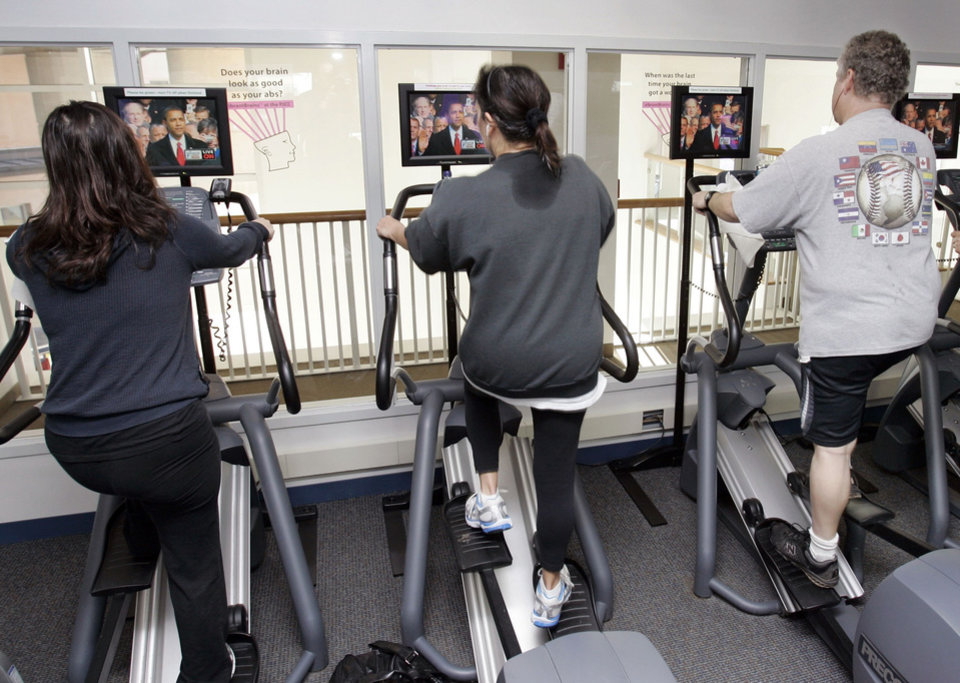 Photo - People workout at the Peninsula Jewish Community Center in Foster City, Calif., as they watch on television the presidential inauguration of President Barack Obama, Tuesday, Jan. 20, 2009.  (AP Photo/Paul Sakuma)