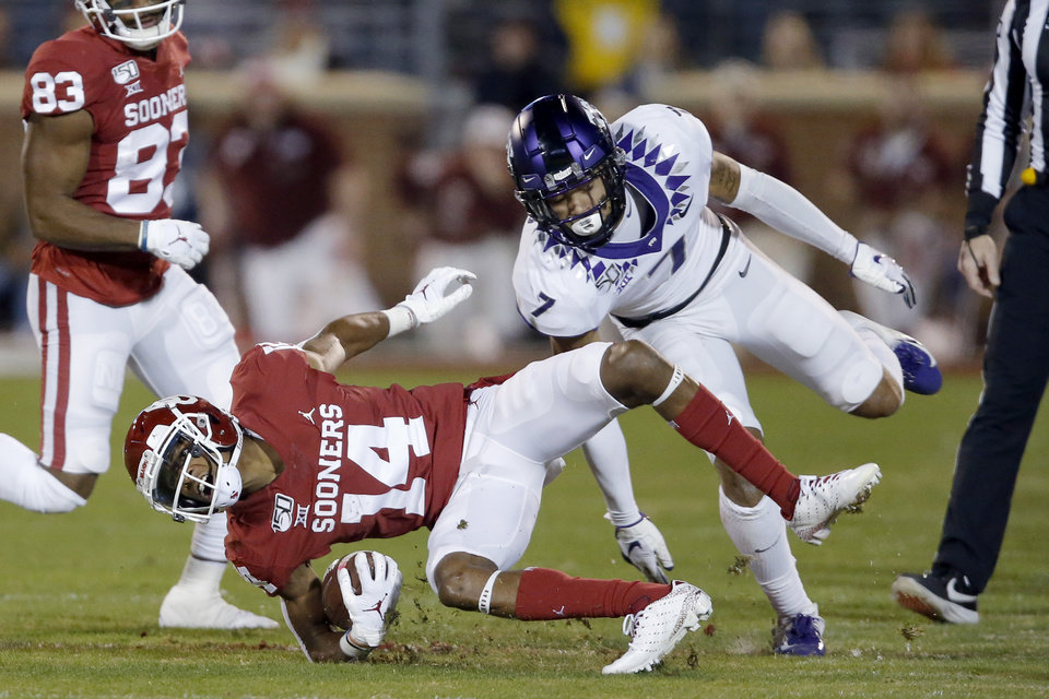 Photo - Oklahoma's Charleston Rambo (14) is brought down by TCU's Trevon Moehrig (7) during an NCAA football game between the University of Oklahoma Sooners (OU) and the TCU Horned Frogs at Gaylord Family-Oklahoma Memorial Stadium in Norman, Okla., Saturday, Nov. 23, 2019. [Bryan Terry/The Oklahoman]