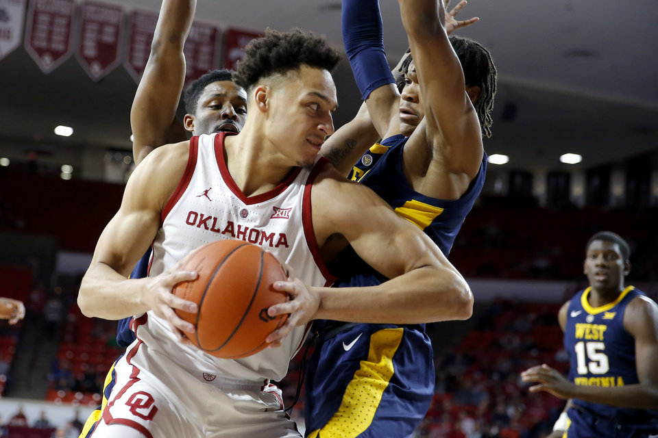 Photo - Oklahoma's Jamuni McNeace (4) tries to get past West Virginia's Brandon Knapper (2) and Trey Doomes (0) during an NCAA college basketball game between the University of Oklahoma (OU) and West Virginia at Lloyd Noble Arena in Norman, Okla.,  Saturday, March 2, 2019. Photo by Bryan Terry, The Oklahoman