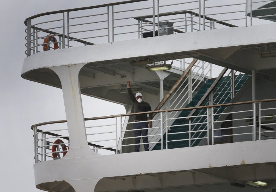 Photo -  A man wearing a mask to protect himself against the spread of coronavirus raises his fist aboard a passenger ship docked at a pier in in the port of Piraeus, near Athens, Friday, April 3, 2020. Greek authorities say a more than 100 people on board the ship have been confirmed as tested positive for the new coronavirus.  The ship, a ferry chartered to house workers from various countries who were to work on a shipbuilding project in Spain, has been anchored outside Greece's main port of Piraeus for several days. Those who have tested positive will be quarantined for 14 days on board the ship. (AP Photo/Lefteris Pitarakis)