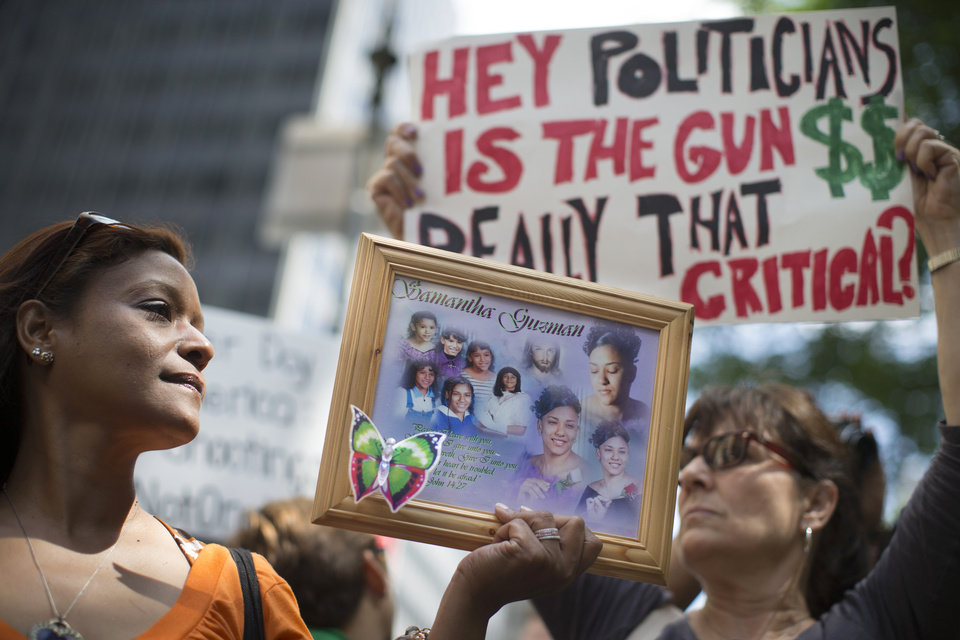 Photo - Diana Rodriguez, of Staten Island, holds a framed image of her daughter Samantha Guzman who was a victim of gun violence, at a rally outside city hall to call for tougher gun control laws, Saturday, June 14, 2014, in New York. The protest was underwritten by former New York Mayor Michael Bloomberg, one of the most visible gun control advocates in the U.S., and included relatives of some of those slain in the 2012 shooting rampage at Sandy Hook Elementary School in Newtown, Conn. (AP Photo/John Minchillo)