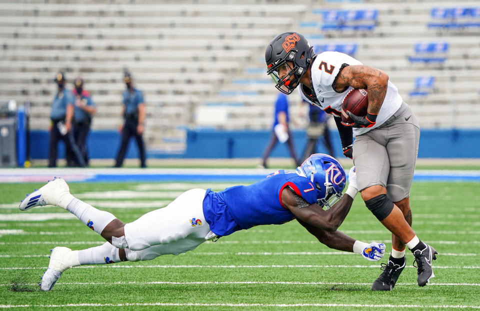 Photo - Oct 3, 2020; Lawrence, Kansas, USA; Oklahoma State Cowboys wide receiver Tylan Wallace (2) runs against Kansas Jayhawks safety Davon Ferguson (7) during the first half at David Booth Kansas Memorial Stadium. Mandatory Credit: Jay Biggerstaff-USA TODAY Sports