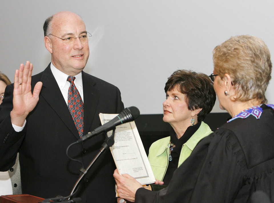 Ray Vaughn takes the oath of office for County Commissioner, District 3, from Oklahoma Supreme Court Justice Yvonne  Kauger, right, as wife Suzanne looks on, Tuesday, January 2, 2007. This was in the Noble Theater at the Oklahoma City Museum of Art.   BY DAVID MCDANIEL, THE OKLAHOMAN.