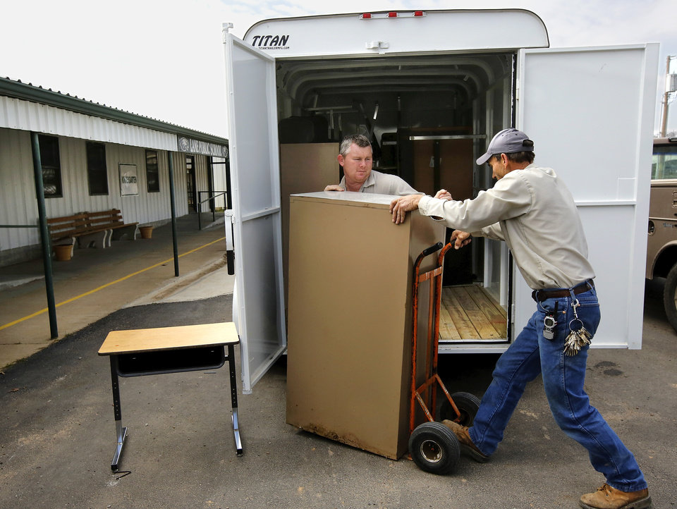 Lane School maintenance workers unload  desks, file cabinets and other furniture pieces removed from Farris School and will be used in Lane School. About 50 students transferred to Lane Public School after their former school, Farris School, was annexed by Lane in Atoka County.   Photo taken  March 1, 2013. Photo by Jim Beckel, The Oklahoman