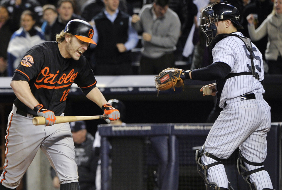 Photo -   Baltimore Orioles' Mark Reynolds (12) reacts after striking out as he walks past New York Yankees catcher Russell Martin (55) during the eighth inning of Game 5 of the American League division baseball series Friday, Oct. 12, 2012, in New York. (AP Photo/Bill Kostroun)