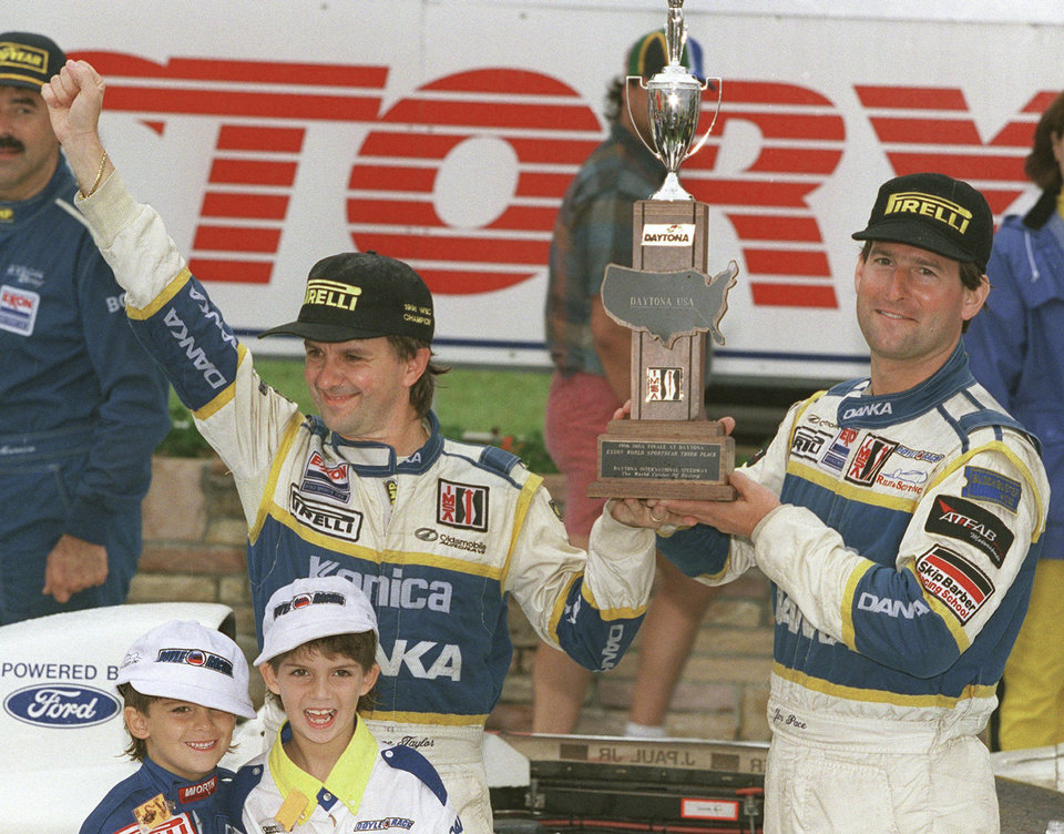Photo - In this 1996 file photo, Wayne Taylor, top left, along with his two sons Jordan, lower left, 5, and Ricky,7, with co-driver Jim Pace celebrate winning the IMSA championship in Victory Lane at Daytona International Speedway in Daytona Beach, Fla. (AP Photo/Daytona Beach News-Journal, Nigel Cook)