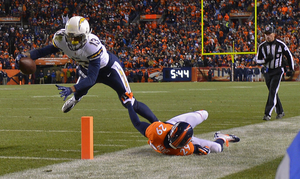 Photo - San Diego Chargers wide receiver Keenan Allen (13) stretches the ball across the goal line for a touchdown against Denver Broncos free safety Michael Huff (29) in the fourth quarter of an NFL AFC division playoff football game, Sunday, Jan. 12, 2014, in Denver. (AP Photo/Jack Dempsey)
