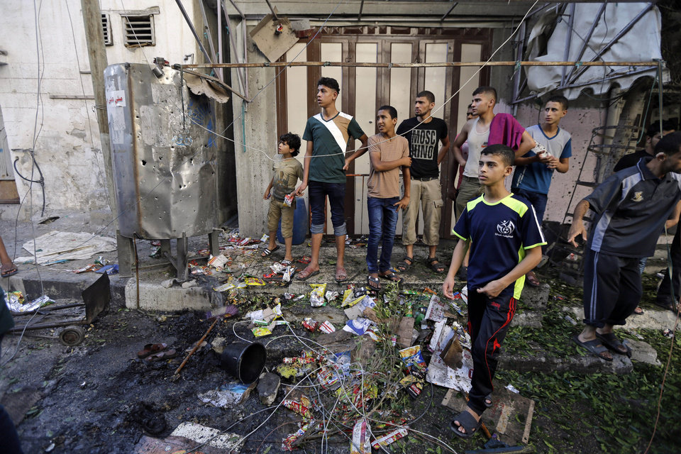 Photo - Palestinians gather at the scene of an explosion that killed 10 people, 9 of them children, at a park at Shati refugee camp, in the northern Gaza Strip, Monday, July 28, 2014. Israeli and Palestinian authorities traded blame over the attack and fighting in the Gaza war raged on despite a major Muslim holiday. (AP Photo/Lefteris Pitarakis)