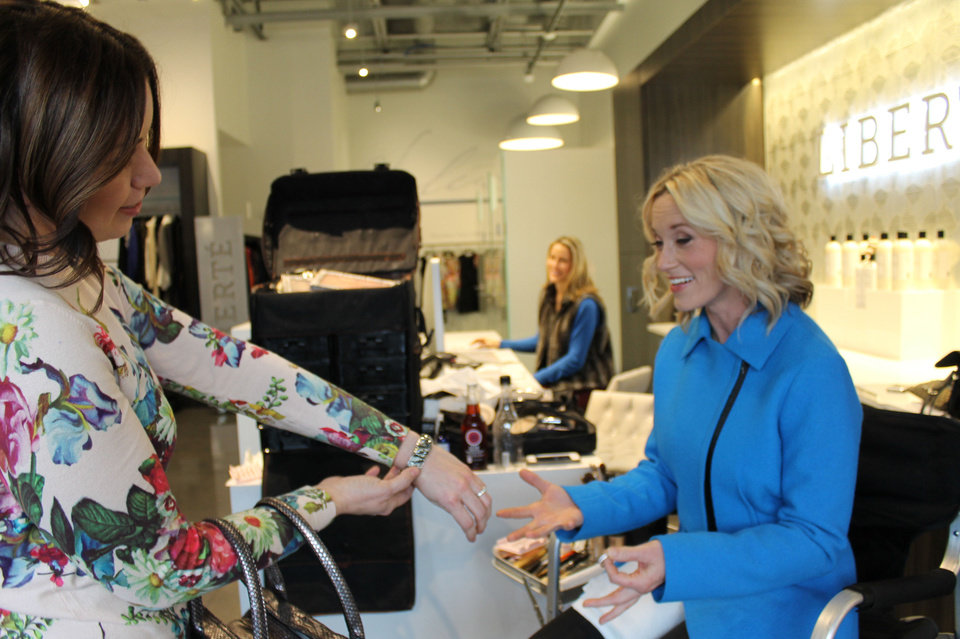 Photo - Danielle Keogh, left, owner of Liberte, gives Christa Gray a bracelet, hoop earrings and handbag to complete her new look. Keogh also donated the outfit Gray wears. Photo by Heather Warlick, The Oklahoman
