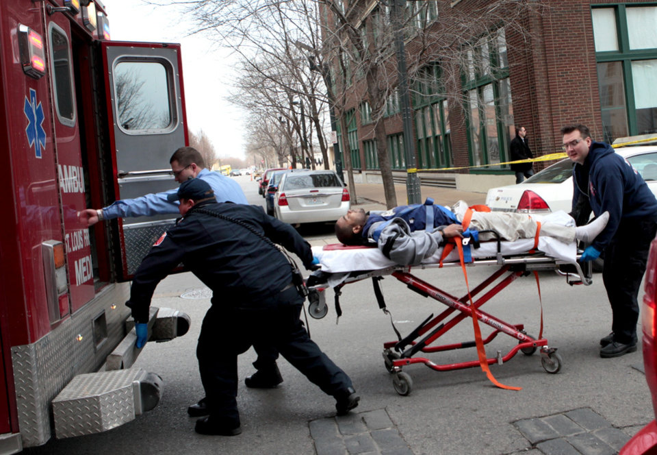 Photo - Police and emergency personnel transport a man to an ambulance after a shooting at Stephens Institute of Business and Arts on Washington Avenue in St. Louis on Tuesday, Jan. 15, 2013.  A part-time student strode into the office of a longtime administrator at the school and shot the man in the chest, creating panic in the school before turning the gun on himself, police said.  (AP Photo/St. Louis Post-Dispatch, David Carson) EDWARDSVILLE INTELLIGENCER OUT; THE ALTON TELEGRAPH OUT