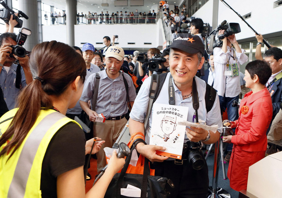 Photo -   In this July 3, 2012 file photo, passengers prepare to board the first flight by Jetstar Japan at Narita International Airport in Narita near Tokyo. Japan has a reputation for loving expensive things like overpriced real estate, gourmet melons and luxury brands. But the nation is finally discovering the joy of flying cheap, with the arrival this year of three low-cost carriers. The takeoff of AirAsia Japan, Peach Aviation and Jetstar Japan could change lifestyles. (AP Photo/Kyodo News, File) JAPAN OUT, MANDATORY CREDIT, NO LICENSING IN CHINA, FRANCE, HONG KONG, JAPAN AND SOUTH KOREA