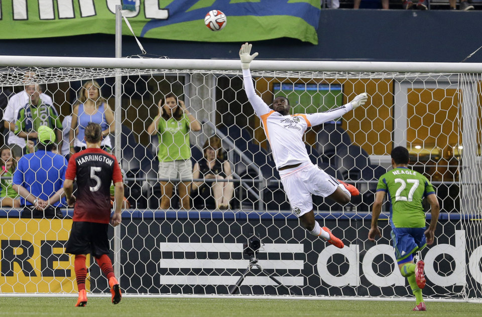 Photo - Portland Timbers goalkeeper Donovan Ricketts, center, leaps for a shot that went over the net as Seattle Sounders' Lamar Neagle, right, and Timbers' Michael Harrington (5) look on in the first half of an MLS soccer match, Sunday, July 13, 2014, in Seattle. (AP Photo/Ted S. Warren)