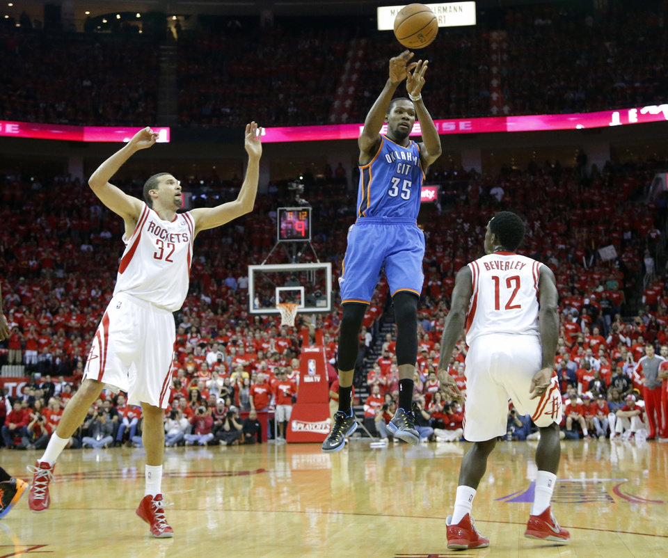 Photo - Oklahoma City's Kevin Durant passes the ball from between  Houston's Francisco Garcia, left, and Patrick Beverley during Game 6 in the first round of the NBA playoffs between the Oklahoma City Thunder and the Houston Rockets at the Toyota Center in Houston, Texas, Friday, May 3, 2013. Photo by Bryan Terry, The Oklahoman