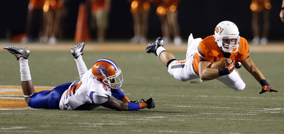 Photo - Oklahoma State's Caleb Muncrief (2) is tripped up by Savannah State's John Wilson (4) during a college football game between Oklahoma State University (OSU) and Savannah State University at Boone Pickens Stadium in Stillwater, Okla., Saturday, Sept. 1, 2012. Photo by Sarah Phipps, The Oklahoman