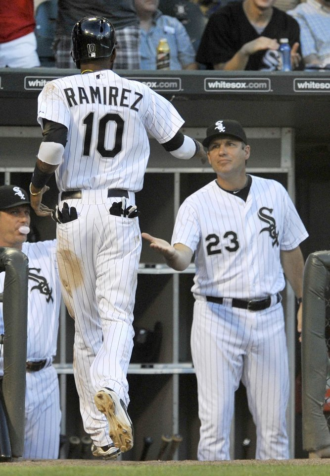 Photo - Chicago White Sox's Alexei Ramirez (10) returns to the dugout and greetings from manager Robin Ventura (23), after scoring on a two-run double by Alex Rios during the third inning of a baseball game against the Atlanta Braves in Chicago, Friday, July 19, 2013. (AP Photo/Paul Beaty)