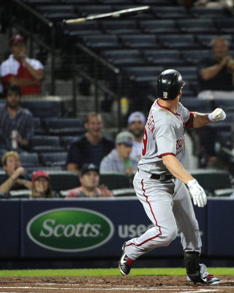 Photo - Washington Nationals' Kevin Frandsen loses his bat as it flies into the stands before hitting a fan, top left, during the seventh inning of a baseball game against the Atlanta Braves on Friday, Aug. 8, 2014, in Atlanta. (AP Photo/David Tulis)