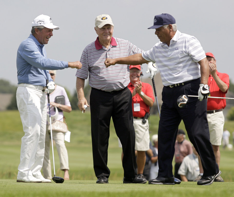 Photo - Gary Player, left, and Lee Trevino bump fists while Jack Nicklaus looks on as they participate in the Greats of Golf Challenge during the second round of the Champions Tour's 3M Championship golf tournament at TPC Twin Cities in Blaine, Minn., Saturday, Aug. 2, 2014. AP Photo/Paul Battaglia)