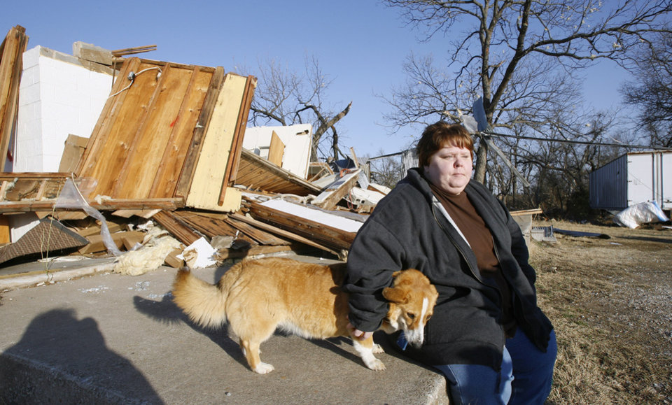 Photo - Trina Quinton sits with a lost dog at her cousin's destroyed furniture store, John's Furniture, on the north side of SH 70 in Lone Grove, Wednesday, Feb. 11, 2009. BY PAUL B. SOUTHERLAND, THE OKLAHOMAN