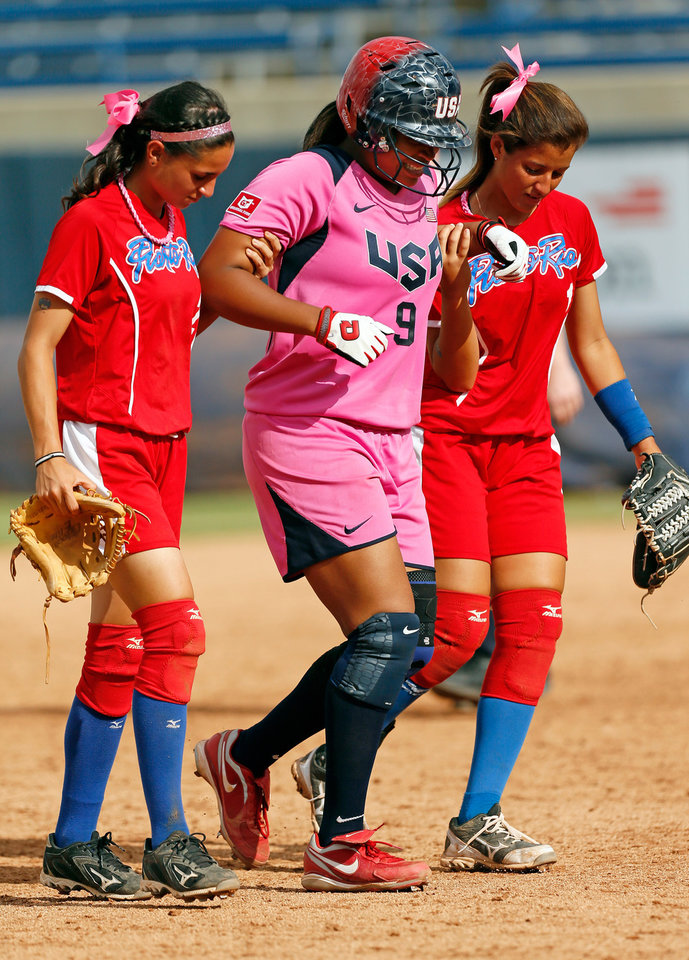 Photo -  Amber Freeman (9) of the United States is helped around the bases by Galis Lozada (2), left, and Dayanira Diaz (1) of Puerto Rico after Freeman hurt herself running the bases on a home run in the fifth inning during a game in the World Cup of Softball between the USA and Puerto Rico at ASA Hall of Fame Stadium in Oklahoma City, Sunday, July 14, 2013. Team USA won, 10-3 in five innings. Photo by Nate Billings, The Oklahoman